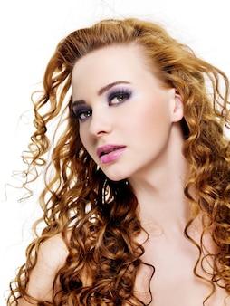 Bardzo młoda kobieta twarz z długimi włosami uroda i stylowy fioletowy makijaż - na białym tle