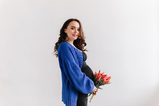Bardzo młoda kobieta w ciąży trzyma tulipany. brunetka dziewczyna w niebieski kardigan i czarna sukienka pozuje z bukietem na na białym tle.