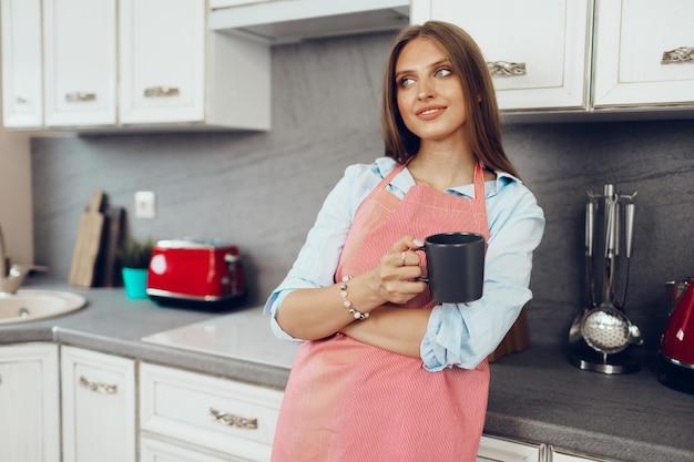 Bardzo młoda kobieta w czerwonym fartuchu, ciesząc się filiżanką kawy w swojej kuchni