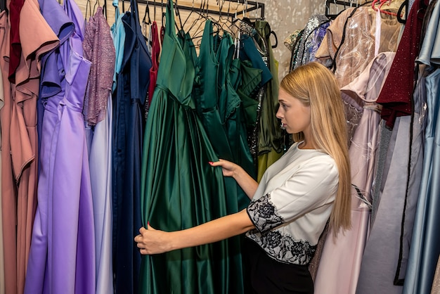 Bardzo młoda kobieta wybierając elegancki strój wieczorowy w sklepie odzieżowym. moda