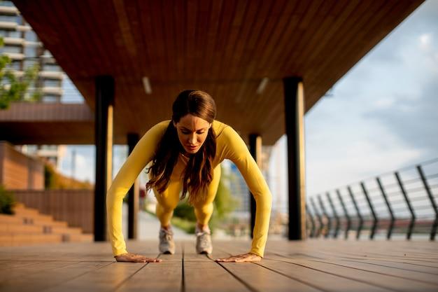 Bardzo młoda kobieta wykonywania pompek na drewnianym chodniku nad rzeką