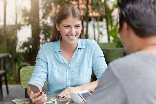 Bardzo młoda kobieta z długimi włosami, siedząc w kawiarni z telefonem i człowiekiem