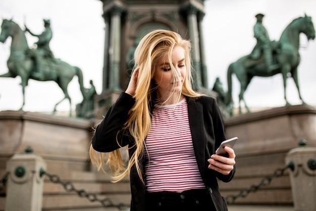 Bardzo młoda kobieta z telefonu komórkowego na ulicy w wiedniu, austria