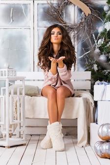 Bardzo młoda seksowna kobieta w dużym różowym swetrze z dzianiny pozowanie w urządzonym zimowym lesie studio. świąteczny nastrój. falowana fryzura. seksowne body