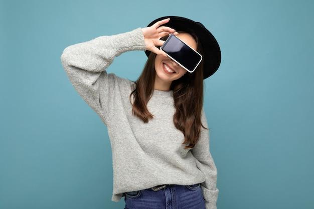 Bardzo młoda uśmiechnięta kobieta ma na sobie czarny kapelusz i szary sweter trzymając telefon patrząc na kamery
