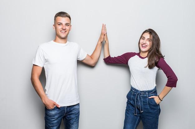 Bardzo młody przystojny chłopak para i dziewczyna daje pięć na białym tle