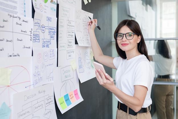 Bardzo młody trener biznesu ze smartfonem przygotowuje się do seminarium, stojąc przy tablicy z papierami