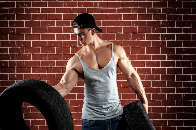 Bardzo muskularny przystojny seksowny facet trzyma gumową oponę i biel, na tle cegły.