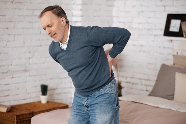 Bardzo nagłe. starszy mężczyzna odczuwa dyskomfort stojąc z powodu bólu pleców.
