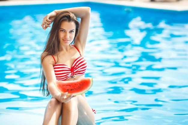 Bardzo piękna kobieta z arbuzem w basenie