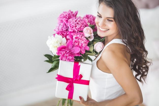 Bardzo piękna kobieta z kwiatami i prezentem w pomieszczeniu
