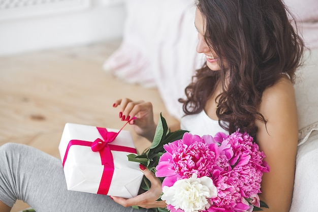 Bardzo piękna kobieta z piwonią i pudełkiem prezentowym w pomieszczeniu