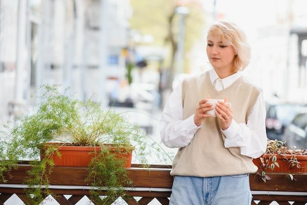 Bardzo piękna młoda kobieta, siedzieć w kawiarni i pić kawę lub herbatę, widok z przodu ulicy