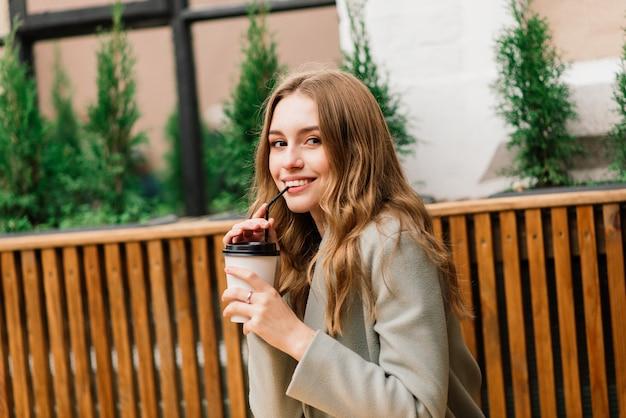 Bardzo piękna młoda kobieta, usiądź w kawiarni i wypij kawę lub herbatę z rogalikiem, widok z przodu na ulicę