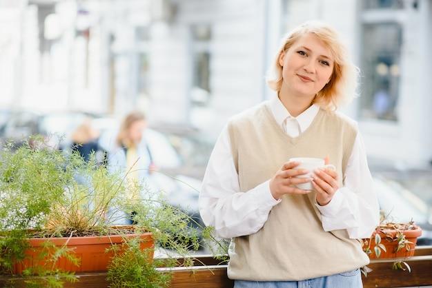Bardzo piękna młoda kobieta, w kawiarni i pić kawę lub herbatę, widok z przodu ulicy