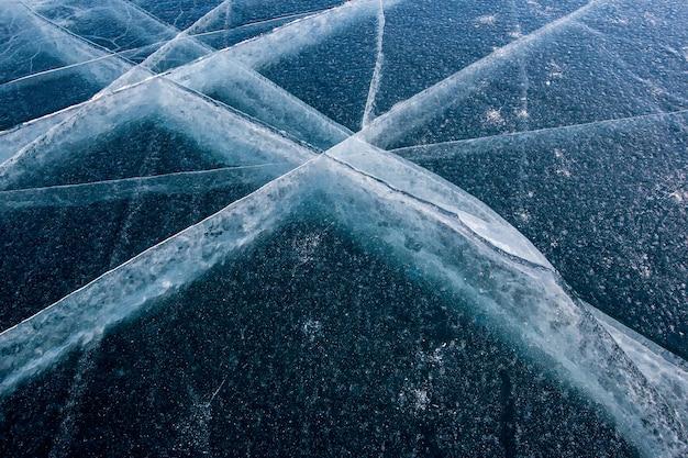 Bardzo piękna naturalna faktura grubego lodu jeziora bajkał z długimi pęknięciami w postaci siatki. ciemny lód i jasne pęknięcia.