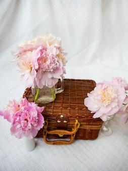 Bardzo piękny bukiet różowych piwonii w wazonie stoi na drewnianej walizce.