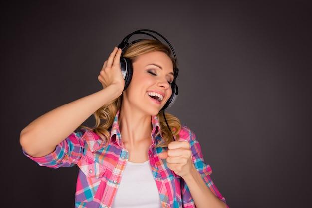 Bardzo podekscytowana dziewczyna w słuchawkach słuchania muzyki i śpiewu