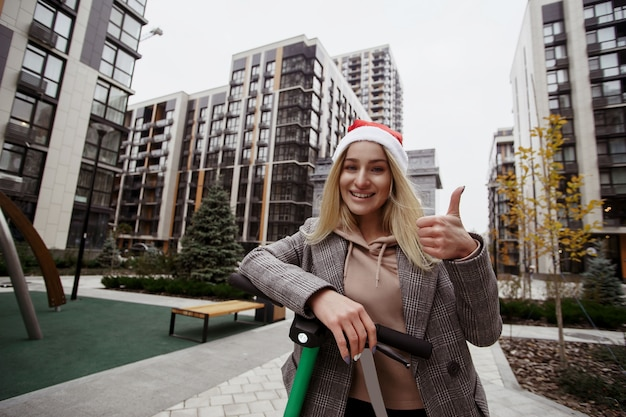 Bardzo podoba mi się ta hulajnoga młoda kobieta w czerwonej czapce świętego mikołaja chętnie korzysta z nowej aplikacji do wypożyczania skuterów na smartfonie. przerwa świąteczna. koncepcja szczęśliwego nowego roku.