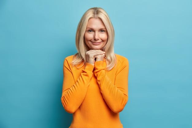 Bardzo pomarszczona kobieta o blond włosach trzyma ręce pod brodą i patrzy prosto w kamerę