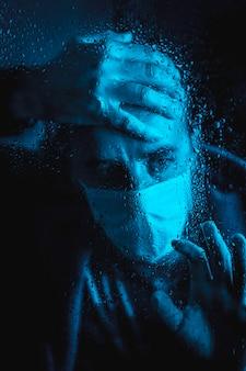 Bardzo przestraszony młody mężczyzna w covid 19 kwarantannie pewnej deszczowej nocy w masce wyglądającej przez okno w niebieskim świetle otoczenia