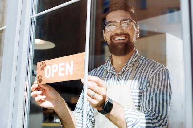 Bardzo przyjacielski. pozytywny szczęśliwy mężczyzna uśmiecha się do ciebie, zapraszając do swojej nowej kawiarni