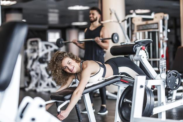 Bardzo seksowna młoda piękna kobieta trenuje i robi ćwiczenia na tyłek w stringach w klubie siłowni