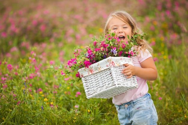 Bardzo śliczna mała emocjonalna dziewczyna uśmiecha się i krzyczy z koszem pełnym kwiatów. radosne dziecko