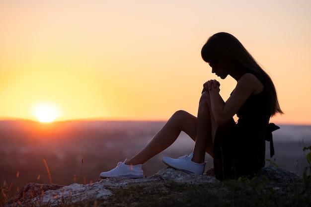 Bardzo smutna kobieta w czarnej krótkiej letniej sukience siedzi na skale, myśląc na zewnątrz o zachodzie słońca. modna kobieta kontemplując w ciepły wieczór na łonie natury.