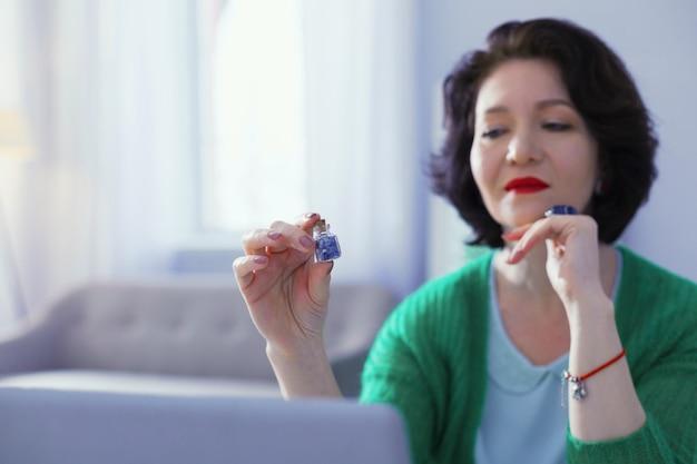 Bardzo specjalny. przyjemna ciemnowłosa kobieta, która ma małą buteleczkę z kamieniami, myśląc o ich szczególnych właściwościach