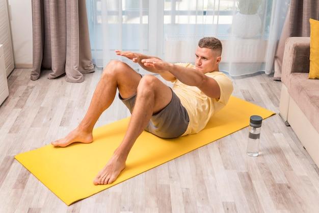 Bardzo sprawny mężczyzna ćwiczy w domu z matą i butelką wody