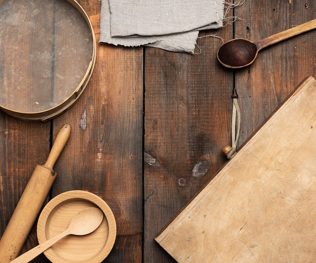Bardzo stara drewniana kuchnia w stylu vintage: sito, wałek do ciasta, puste łyżki i okrągłe talerze na brązowym drewnianym stole, widok z góry