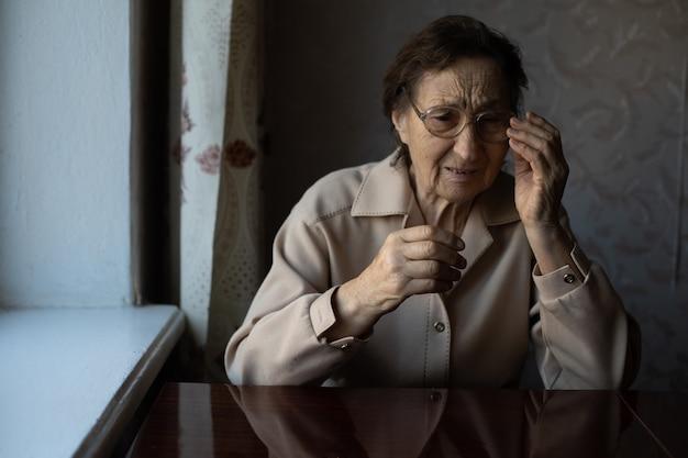 Bardzo stara kobieta zakłada okulary