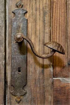 Bardzo stara metalowa klamka i dziurka od klucza na rustykalnych drewnianych drzwiach