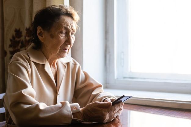 Bardzo stara starsza babcia rasy kaukaskiej z głębokimi zmarszczkami siedzi w domu i używa swojego smartfona na przednim aparacie do prowadzenia wideorozmowy.