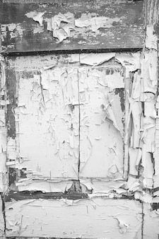 Bardzo stare drewniane drzwi z pękniętą farbą, czarno-białe.