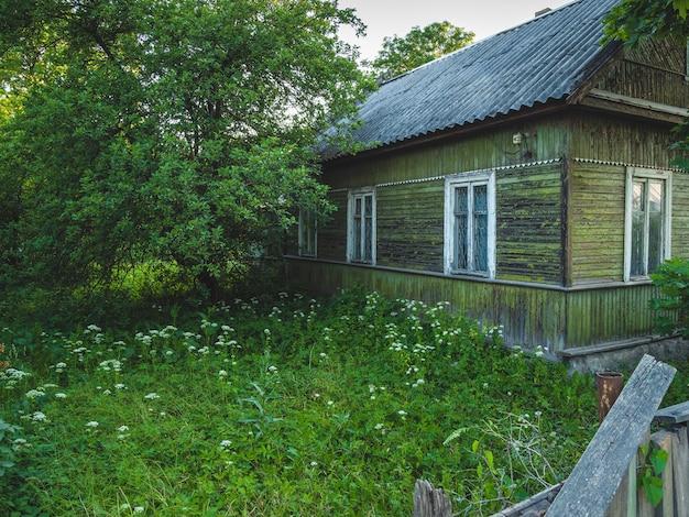 Bardzo stary autentyczny drewniany dom wiejski z zielonym ogrodem
