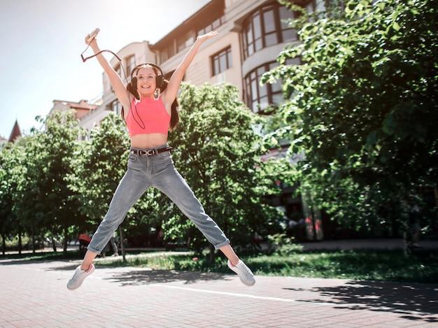 Bardzo szczęśliwa dziewczyna skacze na zewnątrz na ulicę. ma szeroko otwarte ręce i nogi. dziewczyna słucha muzyki i trzyma odtwarzacz muzyki w prawej ręce.