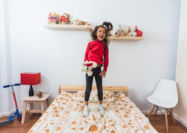 Bardzo szczęśliwa mała dziewczynka w czerwonym swetrze t-shirt z długą szyją, skoki na łóżku.