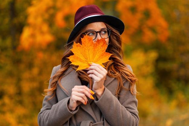 Bardzo szczęśliwa młoda kobieta w stylowych okularach z pozytywnym uśmiechem w eleganckim kapeluszu w długim płaszczu trzyma pomarańczowy liść klonu w pobliżu twarzy. szczęśliwa dziewczyna hipster pozowanie z jesiennym liściem w parku.