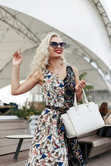 Bardzo szczęśliwa młoda kobieta z okularami przeciwsłonecznymi w nowoczesnej sukni z wzorem na ulicy