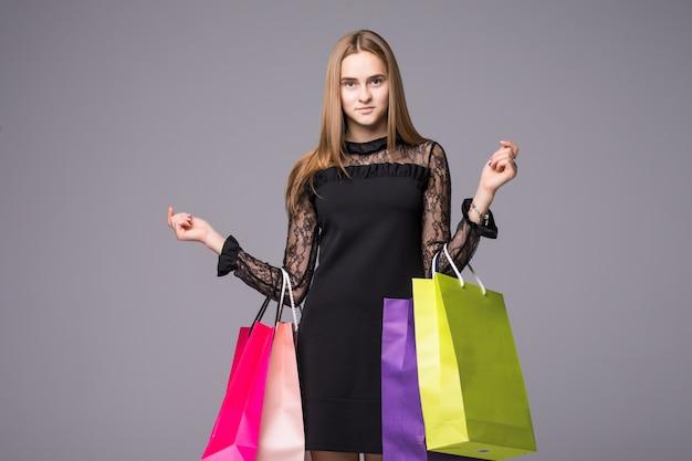 Bardzo szczęśliwa piękna młoda kobieta w koronkowej sukni z torbami na zakupy