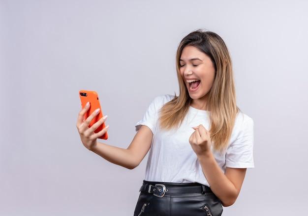 Bardzo szczęśliwa śliczna młoda kobieta w białej koszulce podnosząca zaciśniętą pięść trzymając telefon