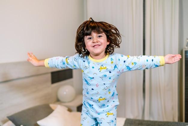 Bardzo szczęśliwe dziecko z otwartymi ramionami skaczące na łóżku w piżamie przed snem