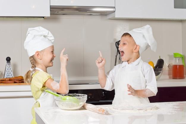 Bardzo szczęśliwe małe dzieci w strojach szefa kuchni bawiące się w kuchni