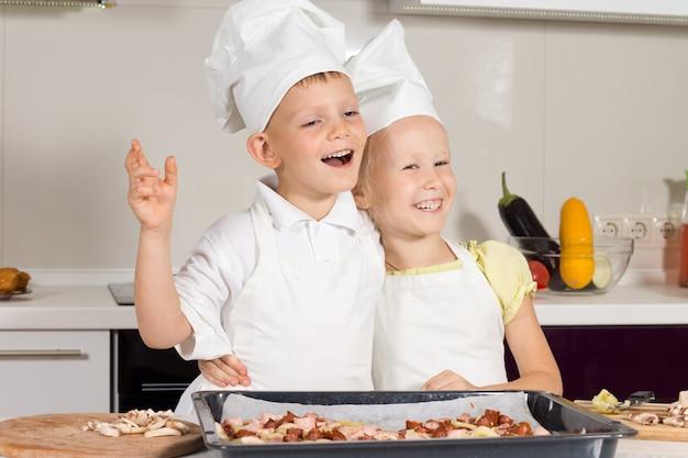 Bardzo szczęśliwi kucharze po upieczeniu pizzy w kuchni.