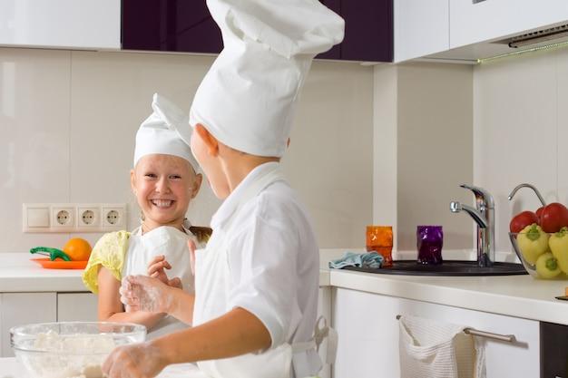 Bardzo szczęśliwi mali kucharze gotują coś do jedzenia w kuchni.