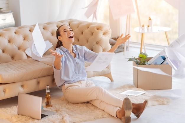 Bardzo szczęśliwy. emocjonalna piękna, radosna kobieta wyglądająca na szczęśliwą z nowej pracy, siedząc na podłodze i wyrzucając swoje stare dokumenty w powietrze