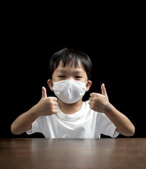 Bardzo szczęśliwy mały chłopiec ubrany w medyczną maskę na twarz pokazuje kciuki do góry