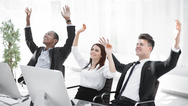 Bardzo szczęśliwy zespół biznesowy siedzi przy biurku